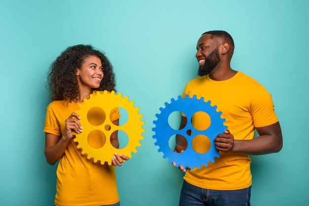 Coppia con ingranaggi in mano sulla parete azzurra. concetto di integrazione, unione, relazione e partenariato