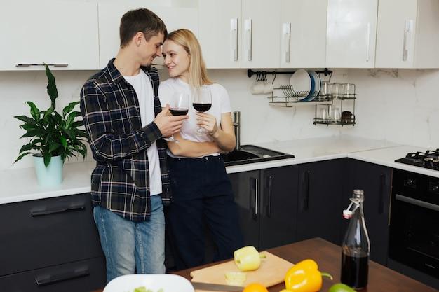 Coppia con bicchieri di vino rosso sta cucinando insalata fresca in cucina