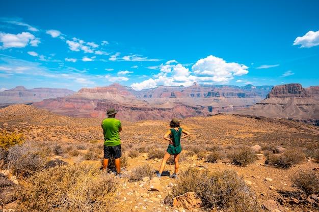 Una coppia con la maglietta verde che riposa sul trekking del sud del sentiero di kaibab. grand canyon
