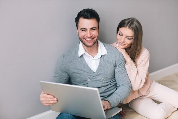 Coppia con un computer portatile seduto sul pavimento. acquisti online.
