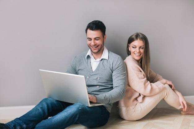 Coppia con laptop sorridente seduto sul pavimento. acquisti online.