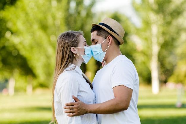 Coppie con la maschera che bacia al parco pubblico
