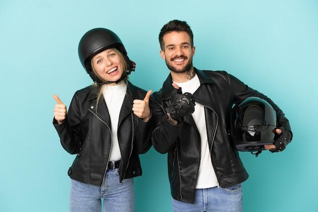 Coppia con casco da motociclista su sfondo blu isolato che fa un gesto di pollice in alto con entrambe le mani e sorride