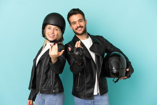 Coppia con casco da motociclista su sfondo blu isolato che invita a venire con la mano. felice che tu sia venuto