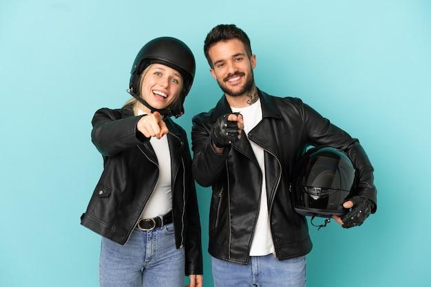Coppia con casco da motociclista su sfondo blu isolato ti punta il dito contro con un'espressione sicura