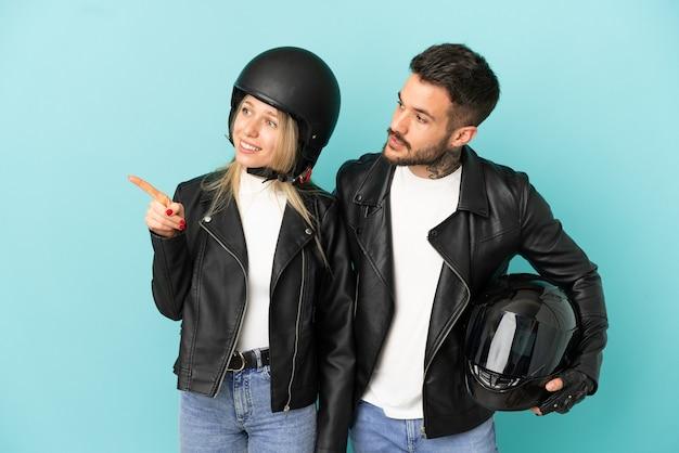 Coppia con casco da motociclista su sfondo blu isolato che presenta un'idea mentre guarda sorridendo verso