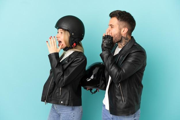 Coppia con casco da motociclista su sfondo blu isolato che grida con la bocca spalancata al laterale
