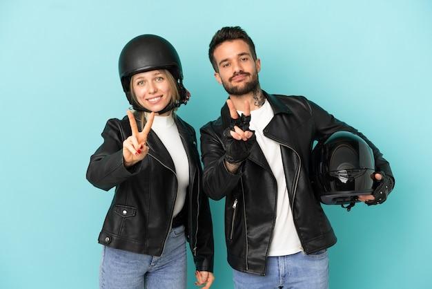 Coppia con casco da motociclista su sfondo blu isolato sorridendo e mostrando il segno della vittoria