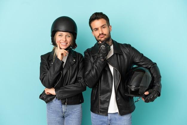 Coppia con casco da motociclista su sfondo blu isolato sorridente con un'espressione dolce