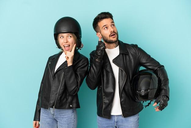 Coppia con casco da motociclista su sfondo blu isolato pensando a un'idea che punta il dito verso l'alto