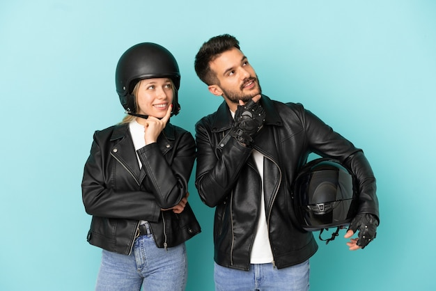 Coppia con casco da motociclista su sfondo blu isolato pensando a un'idea mentre guarda in alto