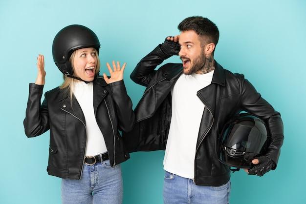 Coppia con casco da motociclista su sfondo blu isolato con espressione facciale sorpresa e scioccata