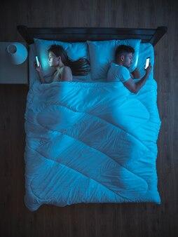 La coppia con il telefono si trova sul letto. notte. vista dall'alto