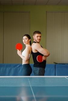 Coppia con racchette pone al tavolo da ping pong con rete al chiuso.