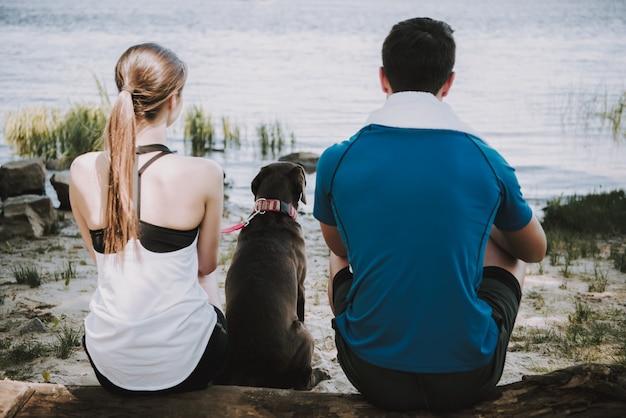 Coppia con il loro cane sulla riva del fiume nel parco verde