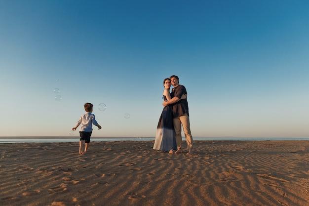 La coppia con il loro figlioletto sta camminando lungo la spiaggia la sera bolle di sapone con luce naturale