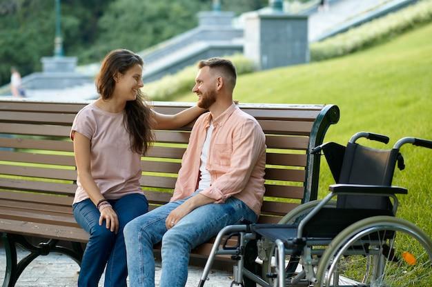 Coppia con sedia a rotelle che si rilassa su una panchina nel parco