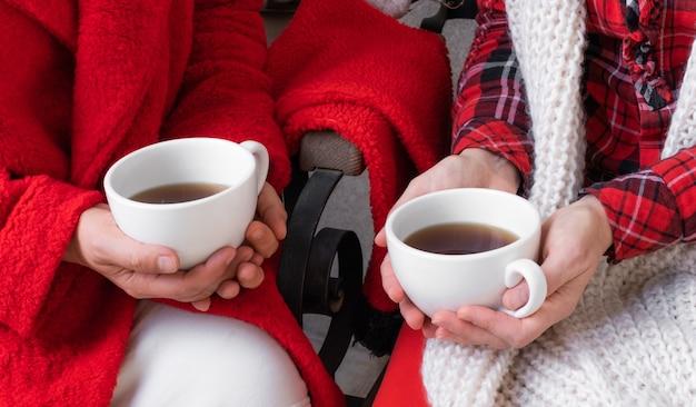 Coppia donna femmina azienda caffè tazza di tè rosso vestiti festivi natale capodanno san valentino