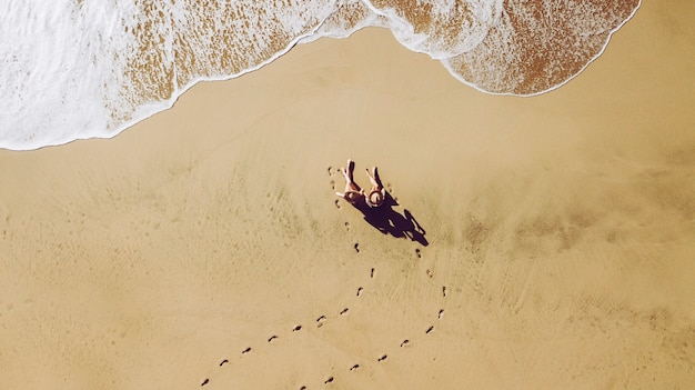 Coppia di donne giovani amici persone in spiaggia viste dalla vista verticale superiore godersi le vacanze estive seduti sulla sabbia per un bagno di sole onde in arrivo e impronte di colori dorati per le vacanze