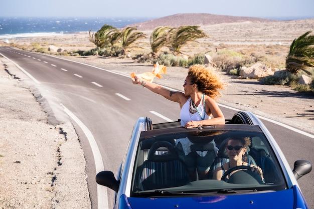 Coppia di giovani donne adulte viaggiano insieme in automobile decappottabile blu in una lunga strada asfaltata con l'oceano in superficie