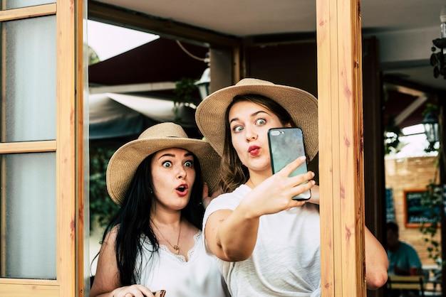 Coppia di giovani ragazze turistiche si fanno selfie con il cellulare e fanno un'espressione simpatica e divertente insieme inviando messaggi