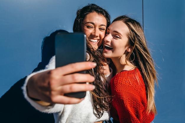 Coppia di giovani ragazze bionde e una bruna che si fanno un selfie con un telefono cellulare su sfondo blu