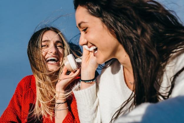 Coppia di giovani ragazze, una bionda e l'altra bruna, ascoltano musica con un grande sorriso