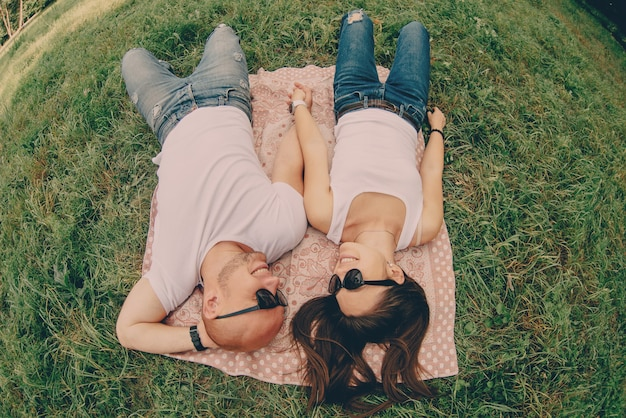 Coppia di giovani amanti in occhiali da sole sono sdraiati sull'erba e sorridente, vista dall'alto