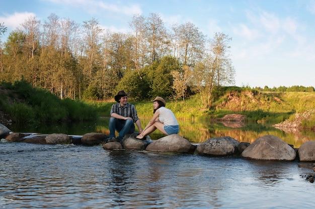 Un paio di giovani ammirano il tramonto in una serata primaverile sul fiume