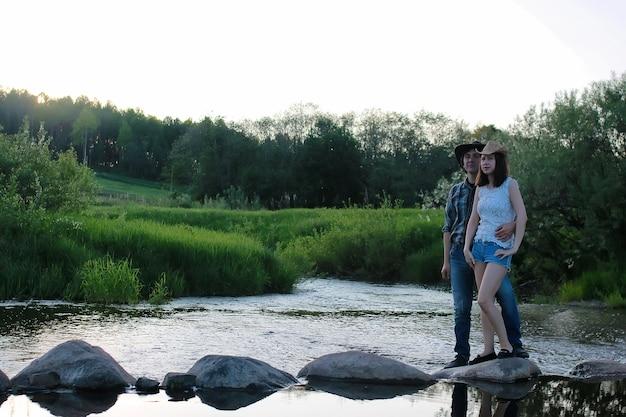 Un paio di giovani ammirano il tramonto in una sera primaverile sul fiume