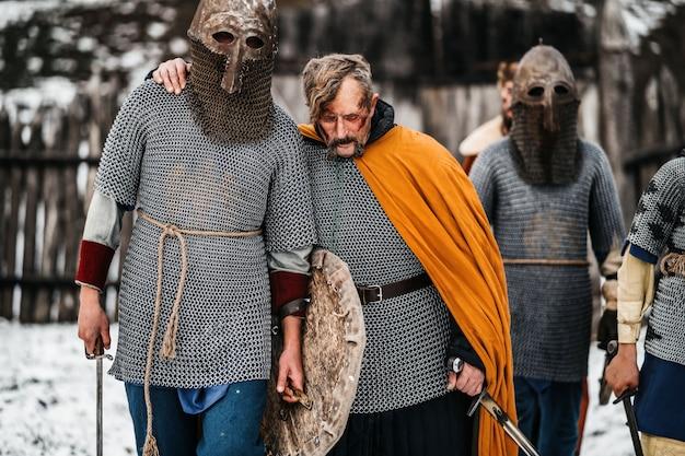 Coraggiosi cavalieri in elmetti e vesti, con le armi in mano, tornano dopo la battaglia. concetto di guerra e storia