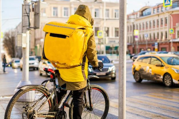 Corriere in bicicletta consegna cibo gustoso nelle strade della città