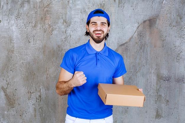 Corriere in uniforme blu che tiene in mano una scatola da asporto e mostra un segno positivo con la mano.