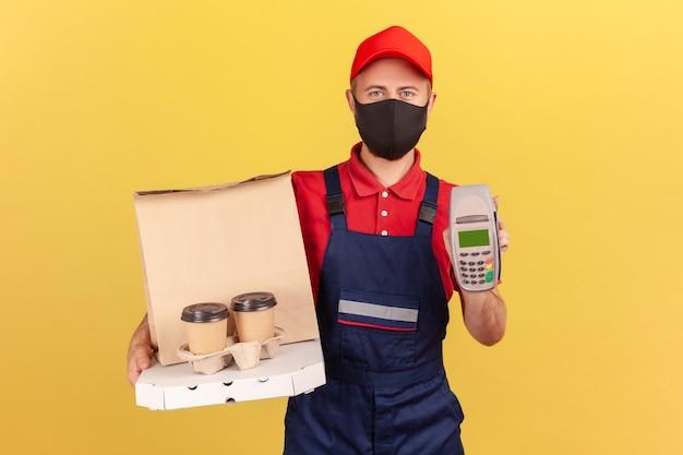 Corriere in uniforme blu e maschera protettiva igienica con terminale pos e caffè con scatola per pizza