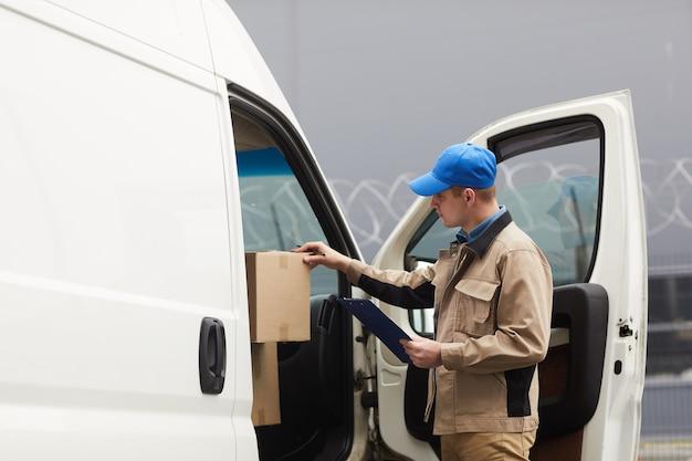 Corriere che controlla le scatole di cartone in macchina prima della spedizione