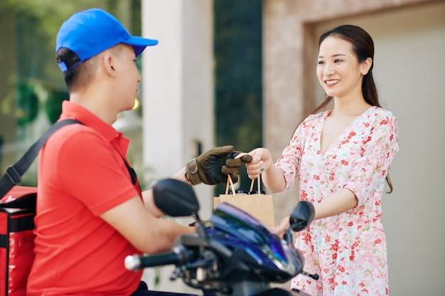 Corriere consegna borsa con cibo delizioso fresco alla giovane donna sorridente
