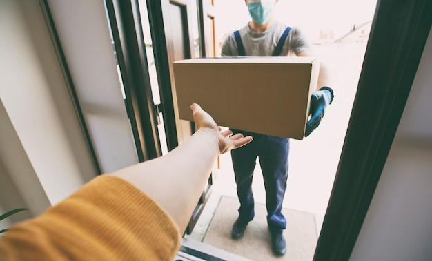 Corriere consegna scatola di cartone a casa indossando guanti in lattice e mascherina medica