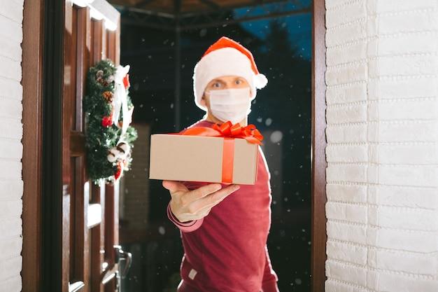 Il corriere consegna un regalo la vigilia di natale con una maschera dal coronavirus
