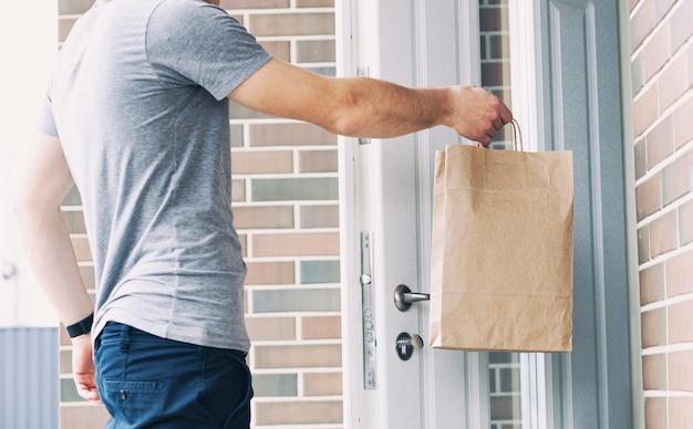 Il corriere consegna l'ordine al cliente alla porta di casa sua