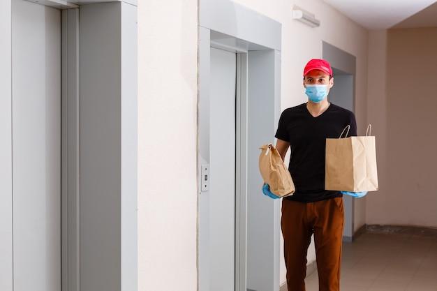 Il corriere consegna il pacco alla porta, in guanti di lattice, consegna contactless durante il periodo di quarantena