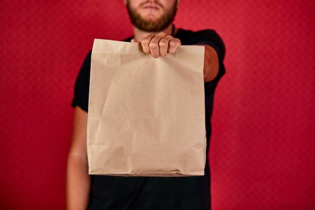 Corriere, fattorino in uniforme nera consegna gli acquisti online in sacchetti di carta marrone