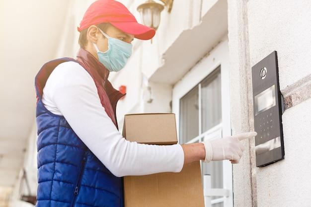 Corriere, fattorino in guanti e maschera in lattice medico consegna in sicurezza gli acquisti online in scatola bianca alla porta durante l'epidemia di coronavirus, covid-19. resta a casa, concetto sicuro.