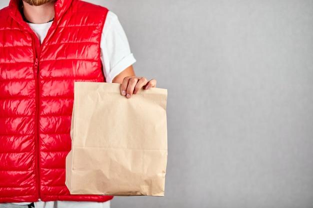 Il corriere, fattorino in divisa rossa, consegna gli acquisti online in sacchetti di carta marroni alla porta, isolata