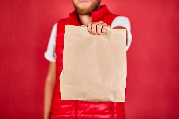 Corriere, fattorino in divisa da giubbotto rosso consegna gli acquisti online in sacchetti di carta marrone