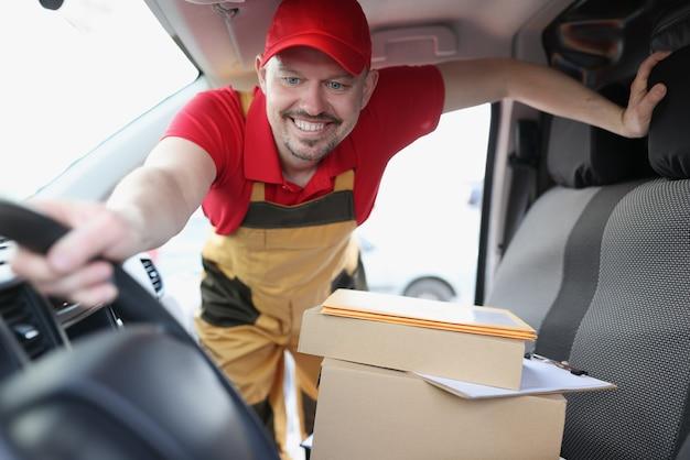 Il corriere raccoglie scatole di cartone in macchina cardboard