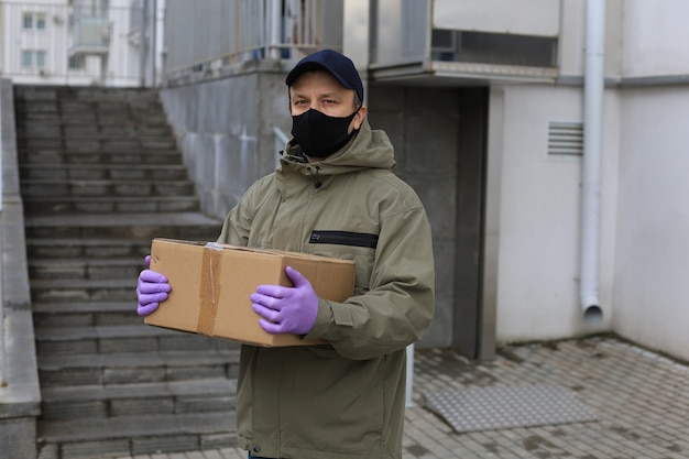 Corriere in maschera facciale e guanti medici che consegnano il pacco. coronavirus e concetto di quarantena.