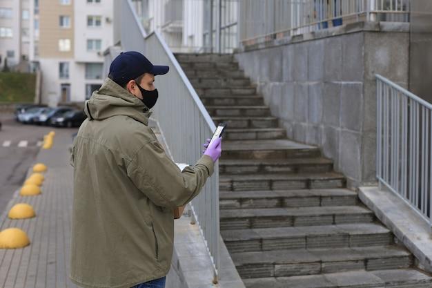 Il corriere in maschera facciale con un pacco all'ingresso di casa verifica le informazioni sullo smartphone. Foto Premium