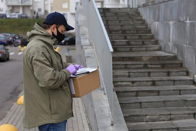 Il corriere in maschera facciale con un pacco all'ingresso di casa verifica le informazioni sullo smartphone.