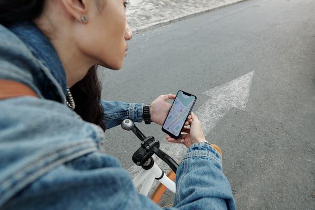 Corriere che segue la mappa sullo smartphone durante la consegna dell'ordine ai clienti
