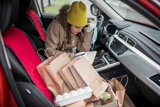 Ragazza del corriere in macchina. servizio di consegna cibo consegna senza contatto, volontario